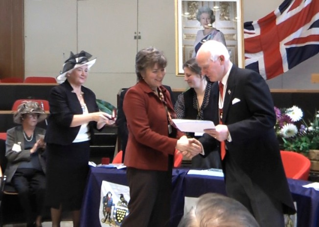 Elizabeth Harper Receiving British Citizenship Certificate From Deputy Lord-Lieutenant, Peter Davies