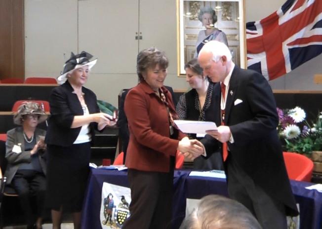 Elizabeth Harper Receiving British Citizenship Certificate From Deputy Lord-Lieutenant, Peter Davies