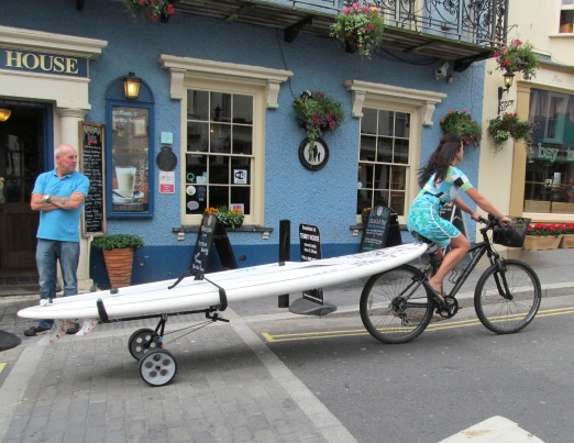 Woman Pulling Surfboard On A Bicycle